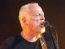 Gilmour singing into a microphone onstage