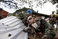 Defense.gov News Photo 111213-A-IP644-027 - U.S. Navy Petty Officer 2nd Class Rejuny Caswell right cuts aluminum panels with Salvadoran marine Patriz Gutierrez for the roof of an open.jpg