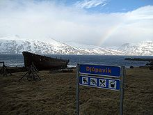 View of the Djúpavík village sign and the wreck of the Suðurland freight ship with Ingólfsfjörður in the background.