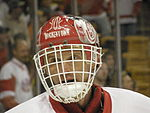 "An ice hockey goaltender is shown from the neck up.  He is wearing a red helmet with a white cage attached to the helmet which covers his face.  The word ""Hockeytown"" can be read on the front of the helmet."