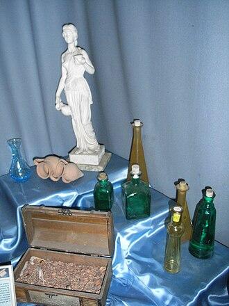 Medicamina Faciei Femineae - Amphorae, scented body oil, perfume bottles (unguentarium), rose petals and a figurine, all from Ancient Rome.