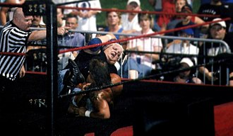 Kid Kash - Kash performing a figure-four leglock on Dusty Rhodes.