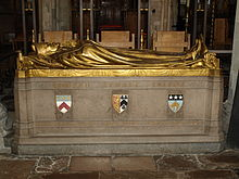 "A stone rectangular monument, with the golden figure of a man dressed in robes and wearing a mitre lying on top, with his hands together in a gesture of prayer. The words ""Edward Stuart Talbot"" on the side in gold, with three shields bearing coats of arms below.  At the bottom, in gold: beneath the first shield, ""1870 Keble 1888""; beneath the second, ""1834–1944""; beneath the third, ""1889 Leeds 1895"""