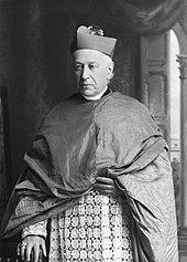 En mand iført mozzetta, liturgiske klæder og brystkors vender fremad.