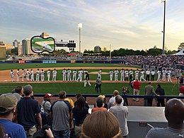 Baseball players in white uniforms with black caps line up along the third base line as they are introduced to the crowd at the ballpark.