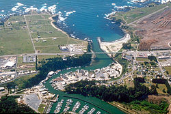 Aerial view of the southern section of Fort Bragg and the mouth of the Noyo River. State Route 1 crosses the river