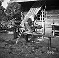 Franc Čukanja, Mihovo 11, s svedrom vrta luknje v čeljust za grablje. Zraven njega več grablšč, zadaj senene vile za seno in lesa voz 1952 (2).jpg