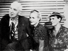 Young woman (center) with older man and woman sitting on each side of her