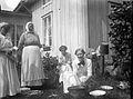 Fyra kvinnor utanför ett hus. Den ena diskar i en balja och de andra hjälper till - Nordiska Museet - NMA.0057503.jpg