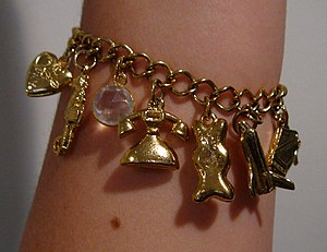 Bracelet - A decorative gold charm bracelet showing a heart-shaped locket, seahorse, crystal, telephone, bear, spaceship, and grand piano.