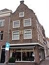 foto van Huis op de hoek van de Brugstraat, met in- en uitgezwenkte topgevel, lelie-ankers, gevelsteen met beeltenis van St.Jacob. Moderne winkelpui