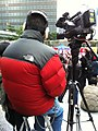 HK Admiralty Voice of Loving Hong Kong media cameraman at work North Face red overcoat Jan-2013.JPG