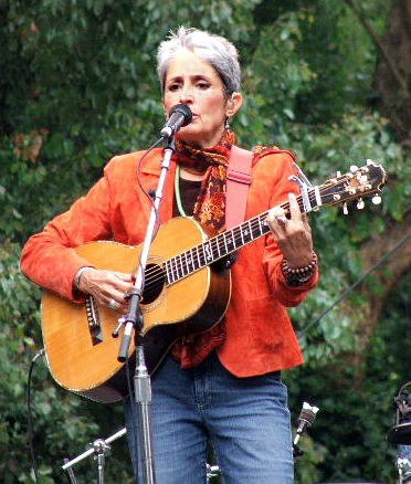 Baez plays in blue jeans and orange waist jacket, against a backdrop of lush trees