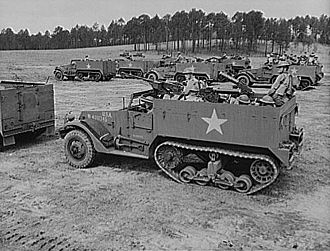 M2 half-track car - M2 at Fort Benning, Georgia, 1942. Note the shorter hull compared to the M3s (left and background) and hinged doors of ammunition compartments in the side armor.