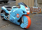 A pale blue motorcycle with a prominent Gulf Oil logo and a unique front fender that encloses almost the entire front wheel on asphalt with a sign in the background that says Young Choppers and Hot Rods.