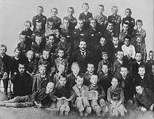 Photo de classe noir et blanc d'une cinquantaine de garçons réunis autour de leur maître d'école; le jeune Hitler se tient debout, au centre de la rangée supérieure.