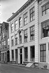 foto van Huis met forse rechte gevel rustend op plint van hardsteen met zwartgeverfde banden en aan weerszijden afgesloten met hoekblokken