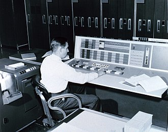 Meteorology - A meteorologist at the console of the IBM 7090 in the Joint Numerical Weather Prediction Unit. c. 1965