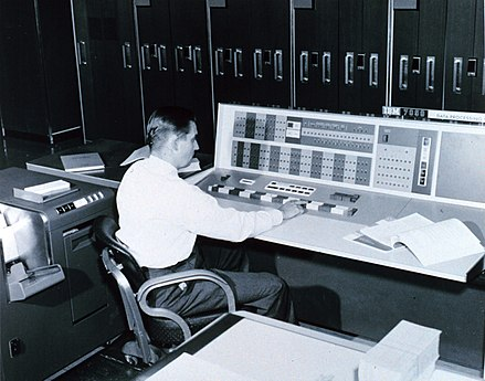A meteorologist at the console of the IBM 7090 in the Joint Numerical Weather Prediction Unit. c. 1965 IBM 7090 console used by a meteorologist, 1965.jpg