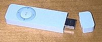 First generation iPod shuffle with the cap removed to show the USB connector. The cap snaps onto the unit. iPod shuffle comes with a second cap on a lanyard which a user can wear around his or her neck.