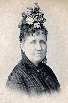 Head and shoulders photograph of a middle-aged Isabel wearing a flower hat