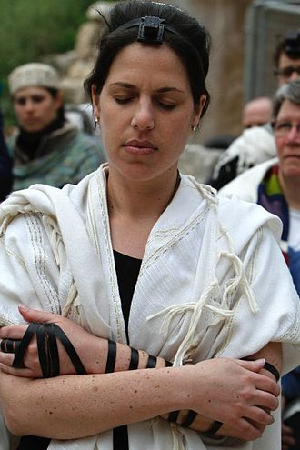 Tefillin - A Jewish woman praying with a tallit and tefillin