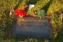 A flat, bronze grave marker surrounded by grass and decorated with flowers and small American flags