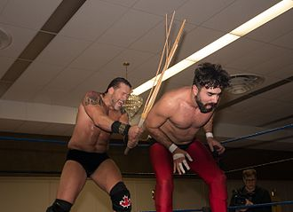 Professional wrestling match types - Johnny Devine (left) uses a kendo stick on Buck Gunderson during a match
