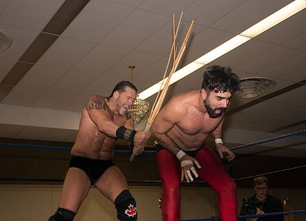 Johnny Devine (left) uses a kendo stick on Buck Gunderson during a match Johnny Devine kendo stick.jpg