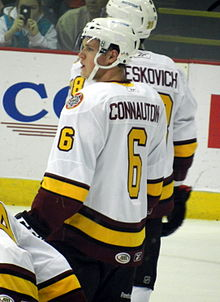 A Caucasian ice hockey player, shown from the waist up, has his back turned to the camera looking over his left shoulder. He wears a white jersey with his name in maroon lettering and the number 6 on his back and sleeve in yellow.