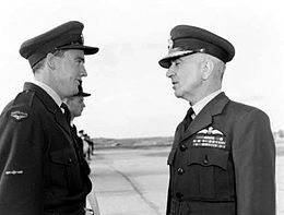 Informal half portrait of two men wearing dark military uniforms with peaked caps, in conversation outdoors