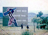 "Two armed East German soldiers, seen through a barbed-wire fence, walking from right to left through a grassy hilly landscape towards a clump of young trees. Behind them is a very large propaganda sign showing a caricature of West German Chancellor Konrad Adenauer clutching a missile while standing on a ladder being propped up by a military officer. The rungs of the ladder are made from the acronym ""NATO"". The sign is captioned: ""Wer hoch hinaus will, fällt tief!"""