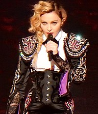 Madonna playing an ukulele and smiling and singing, while looking to her right.