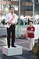 Masahiro Ishida on the podium and canvasser standing beside him. (48206159352).jpg