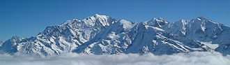panorama of Mont Blanc mountain range above gray clouds under a blue sky