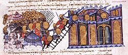 Medieval miniature depicting a city being stormed. To the left is the Byzantine army, with shields and spears, with the tents of their camp to their back, they are scaling ladders onto the walls of a city (right), whose defenders try to fight them off from their top.