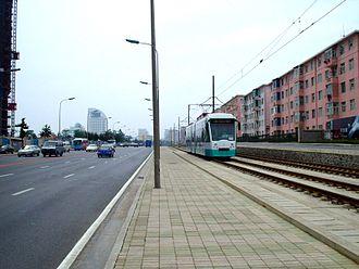 "Trams in Dalian - Low floor type stock of Line 202, on reserved track. Tram type DL6WA, mark Dalianren (meaning ""Dalian people"") manufactured by Tram Factory of Dalian Public Transport Group."