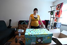 The maternity package, in neutral colors, is seen next to a mother expecting a baby.