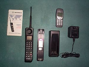 Motorola International 3200 - A Motorola International 3200 mobile phone (bottom), with its manual and charger, and also a Nokia 3210 phone for comparison (top).