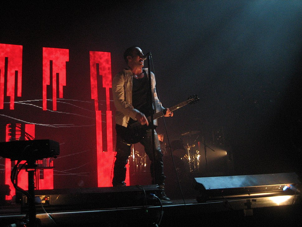 A man playing guitar and singing into a microphone on stage in front of a series of red teeth-like light patterns.
