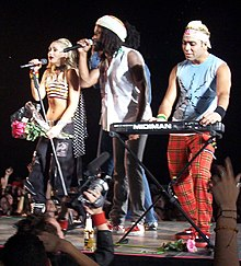 A blonde lady holding a bunch of pink flowers (Stefani), a black man with dreadlocks (McNair) and an Indian man with dyed-blond hair (Kanal) stand on a grey stage. The first two performers are singing into microphones, while the third performer plays a keyboard. In the background, a crowd cheers them. In the foreground, a man holds up a camcorder to film the group.