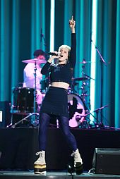 Robyn onstage in black, pointing up