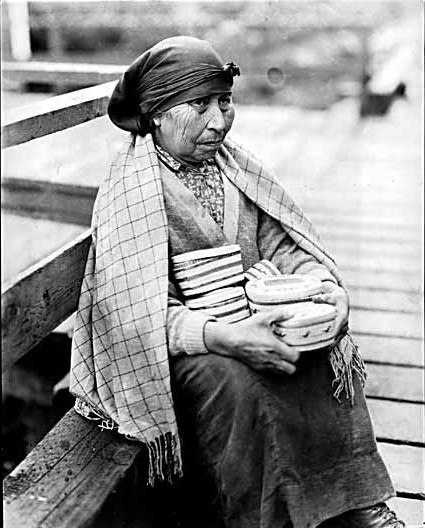 Nootka woman with baskets for sale that she made