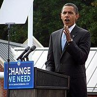 """Een donkere man zichtbaar vanaf de taille gebaren als hij spreekt van een podium.  Hij heeft zeer kort zwart haar en draagt een zwart pak met een wit overhemd en blauwe stropdas eronder.  Hij draagt een horloge aan zijn linkerhand.  Een blauw bord met de woorden """"Change We Need"""" in het wit is aan de voorkant van het podium bevestigd."""