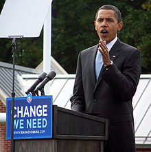 "Obama gestures from the podium while campaigning. The front of the podium has a sign that reads ""Change We Need"" with WWW.BARACKOBAMA.COM below and his campaign logo above."
