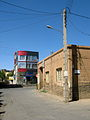 Old brick made house and new aluminium front building - Manuchehri st - Nishapur 5.JPG