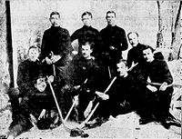 Men wearing hockey sweaters assembled in three rows in front of a painting of a forest scene. Several are holding hockey sticks