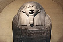 Image of a dark stone Egyptian sarcophagus. The image shows the face of the sarcophagus in a relaxed position looking to the horizon. The sarcophagus shows left-to-right inscriptions in Phoenician on its lid.