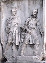 Parthian prisoner in chains, led forward by a Roman, circa 200 AD. Arch of Septimius Severus, Rome.