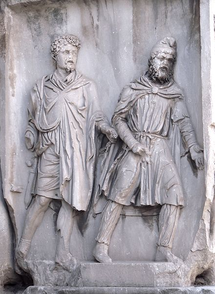 A Parthian (right) wearing a Phrygian cap, depicted as a prisoner of war in chains held by a Roman (left); Arch of Septimius Severus, Rome, 203 AD ParthianInChains.jpg